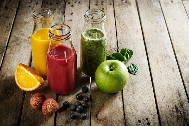 Leckere bunte frische hausgemachte smoothies in gläsern auf holztisch. gesundes, entgiftungskonzept.