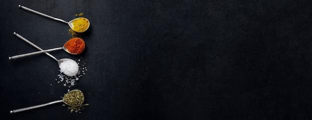 Leckere bunte gewürze in löffeln auf dunklem hintergrund. draufsicht