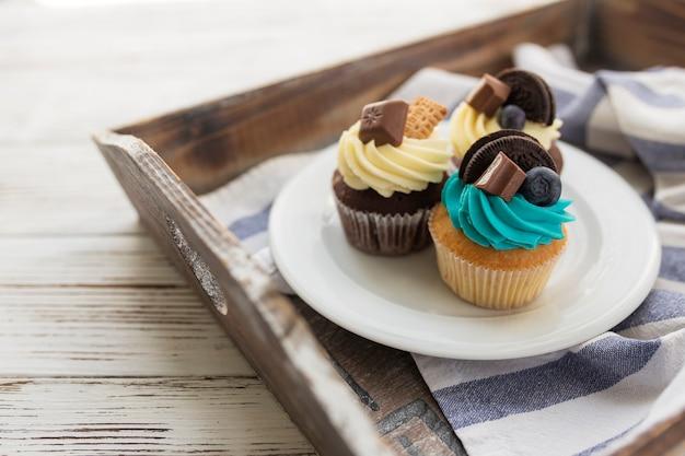 Leckere bunte muffins und cupcakes auf dem weißen teller auf einem holztablett mit handtuch. dekoriert mit verschiedenen bonbons, keksen und farbigem süßem frischkäse.
