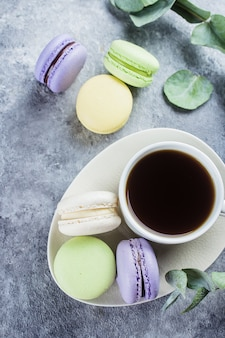 Leckere bunte pastell macarons mit sahne und kaffeetasse. kaffeepauseszene mit macaron süßigkeit