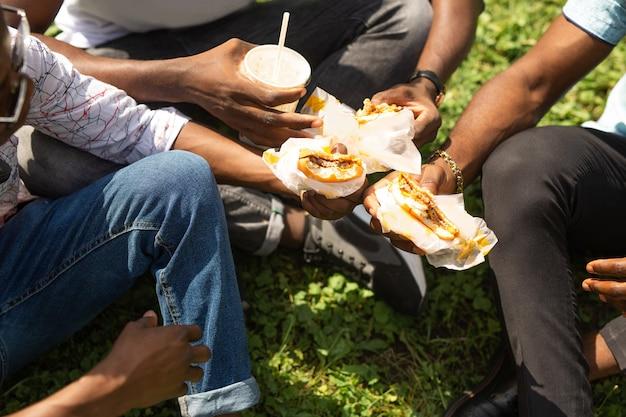 Leckere burger in den händen von drei afrikanern beim sommerpicknick