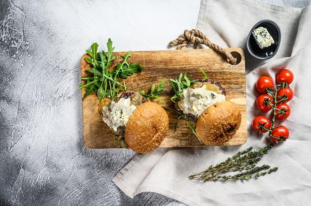 Leckere burger mit blauschimmelkäse, marmorrindfleisch, zwiebelmarmelade und rucola. grauer hintergrund. draufsicht