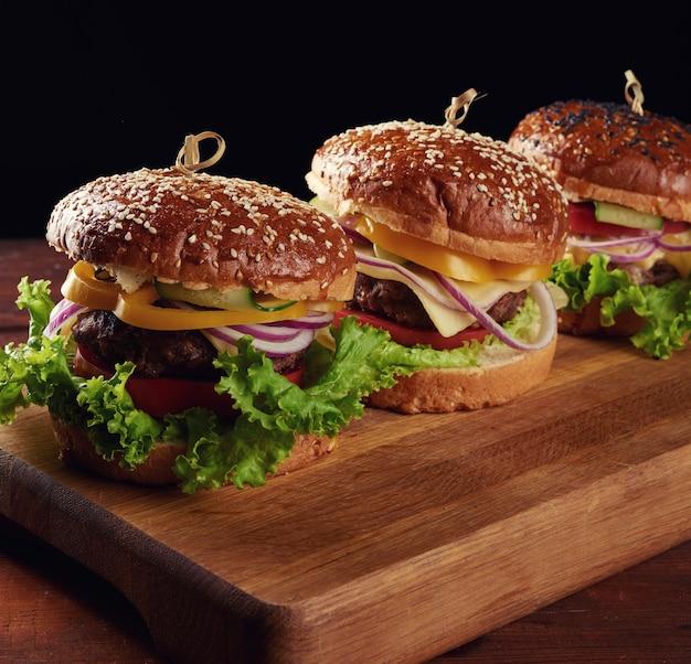 Leckere burger mit gebratenem rinderkotelett, tomaten, salat und zwiebeln, knuspriges weißes weizenmehlbrötchen mit sesam. fast food auf einem holzbrett
