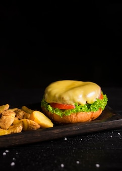 Leckere burger mit geschmolzenem käse und pommes