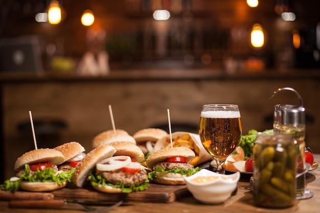 Leckere burger mit grünem salat auf holztisch. leckere burger. pommes frites.