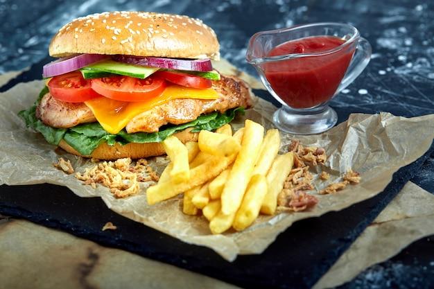 Leckere burger mit rindfleisch, tomaten, käse und pommes frites mit tomatensauce