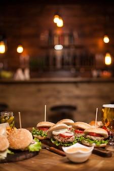 Leckere burger und cheesburger auf einem tisch in einem vintage-pub oder restaurant. im hintergrund sieht man den innenraum verschwommen