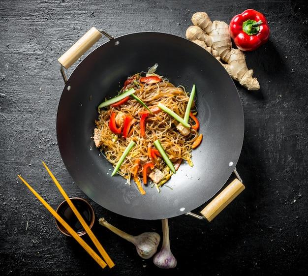 Leckere cellophan-nudeln in einer pfanne wok mit stäbchen. auf schwarzem rustikalem tisch