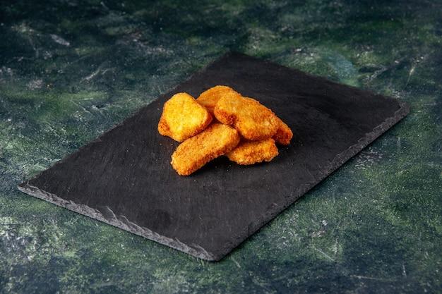 Leckere chicken nuggets auf schwarzem tablett auf dunkler farboberfläche mit freiem platz