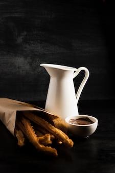 Leckere churros in einer papiertüte und geschmolzener schokolade