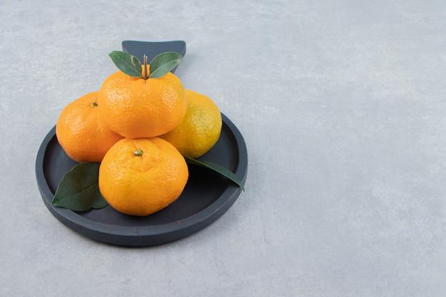 Leckere clementinenfrüchte auf schwarzem brett.