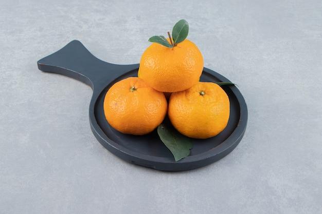 Leckere clementinenfrüchte auf schwarzem brett