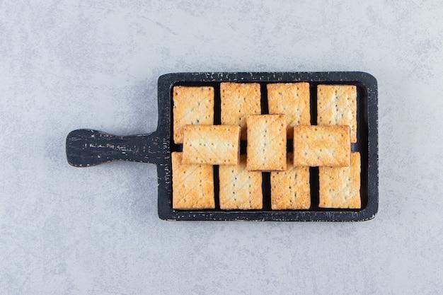 Leckere cracker-kekse gefüllt mit schokolade auf schwarzem schneidebrett.