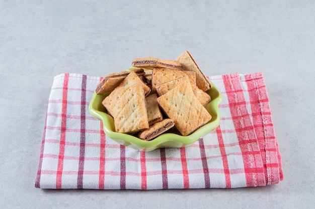 Leckere cracker-kekse gefüllt mit schokolade in grüner schüssel.