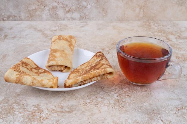 Leckere crepes mit einer tasse leckerem tee