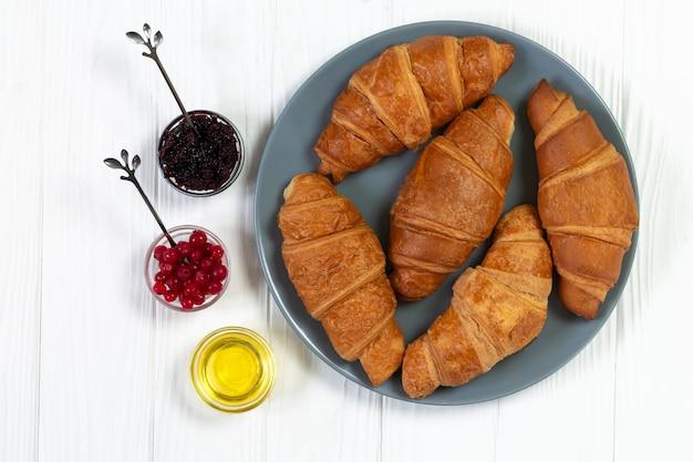 Leckere croissants mit beeren, marmelade und honig auf teller draufsicht. morgenfrühstückskonzept