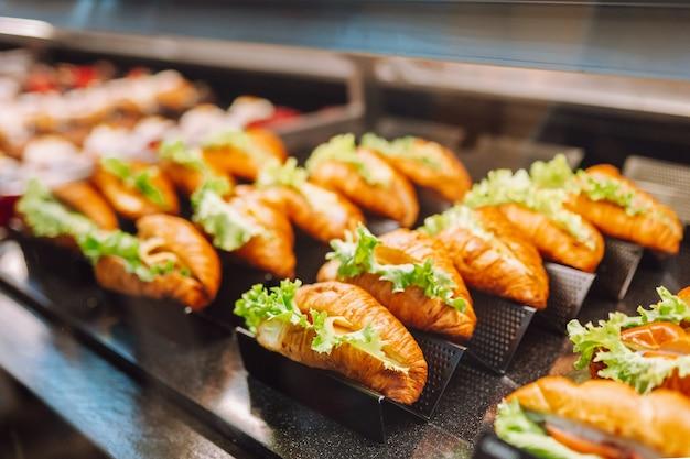 Leckere croissants mit grünem salat auf der ladenvitrine des bäckereihauses