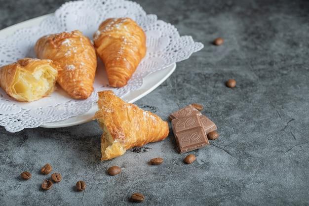 Leckere croissants mit schokolade auf grau.