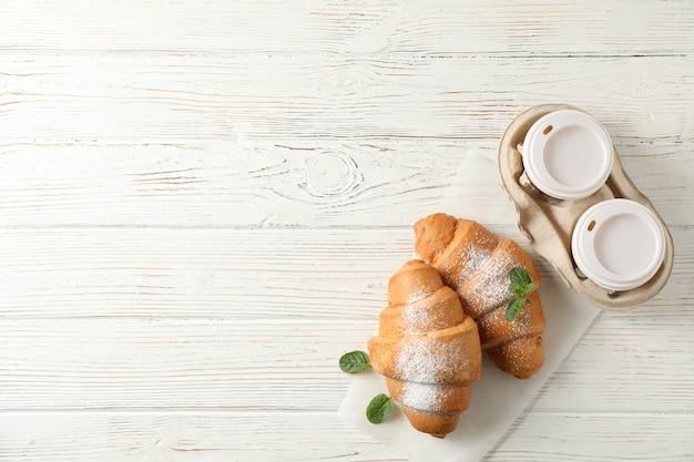 Leckere croissants und tassen mit kaffee auf hölzernem hintergrund, draufsicht