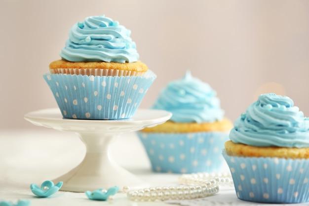 Leckere cupcakes auf tisch auf licht