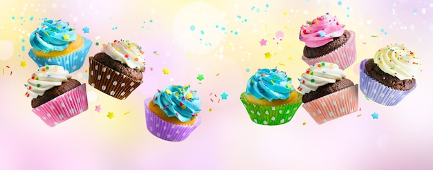 Leckere cupcakes für party, geburtstag. verschiedene cupcakes mit rosa weißer und blauer creme, die über rosa abstrakten hintergrund fliegen flying