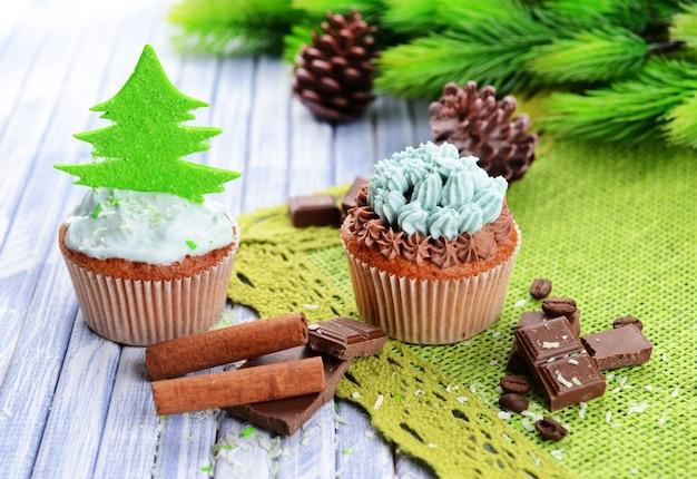 Leckere cupcakes mit buttercreme, auf farbigem holzhintergrund