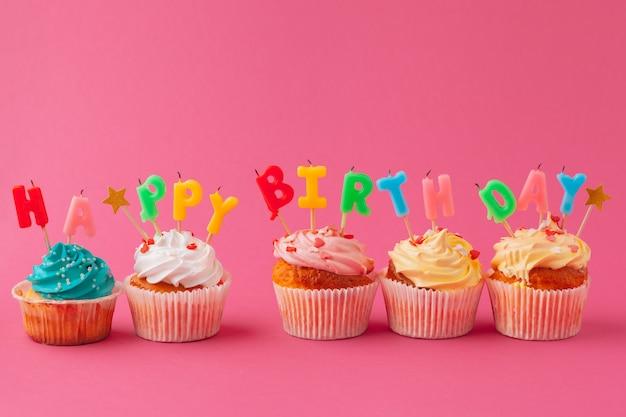Leckere cupcakes mit kerzen auf einem farbigen. festlich, geburtstag