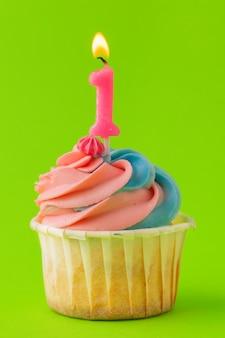 Leckere cupcakes mit kerzen auf einem farbigen. festlicher hintergrund, geburtstag