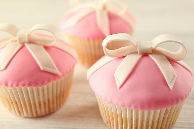 Leckere cupcakes mit schleife, auf hellem hintergrund