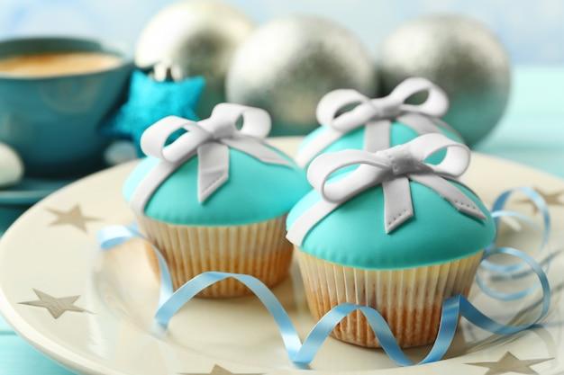 Leckere cupcakes mit schleife, kaffeetasse und weihnachtsspielzeug auf farbigem holztisch