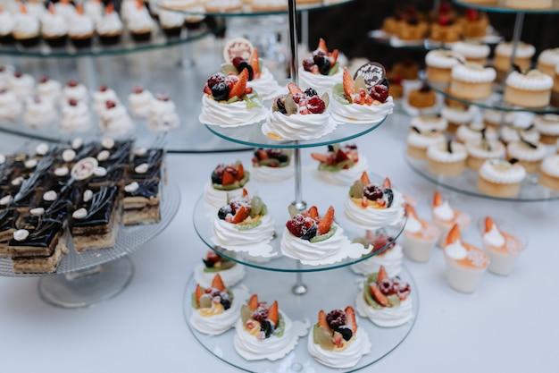 Leckere desserts, kuchen und gebäck am süßen hochzeitsbuffet