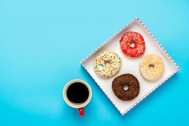 Leckere donuts in einer box und eine tasse mit heißem kaffee auf einer blauen oberfläche. konzept von süßigkeiten, bäckerei, gebäck, kaffeestube. platz. flachgelegt, draufsicht