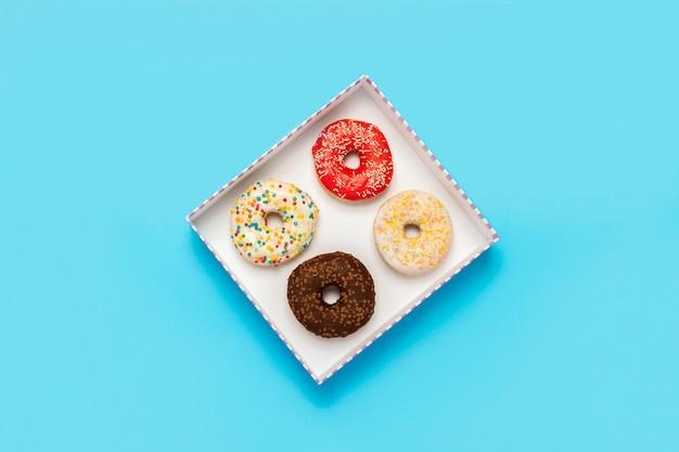 Leckere donuts in einer schachtel auf einem blauen feld. konzept von süßigkeiten, bäckerei, gebäck, café.