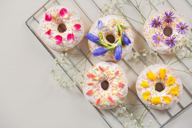 Leckere donuts und blumen auf backblech und licht