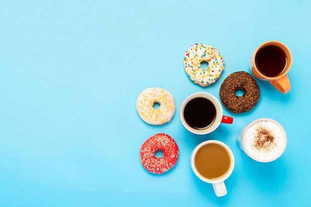 Leckere donuts und tassen mit heißen getränken auf einer blauen fläche. konzept von süßigkeiten, bäckerei, gebäck, café, freunden.