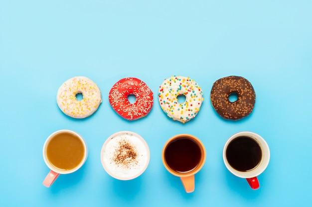 Leckere donuts und tassen mit heißen getränken auf einer blauen fläche. konzept von süßigkeiten, bäckerei, gebäck.