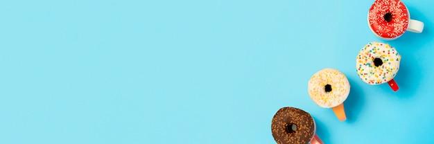 Leckere donuts und tassen mit heißen getränken auf einer blauen oberfläche. konzept von süßigkeiten, bäckerei, gebäck, kaffeestube. . flachgelegt, draufsicht