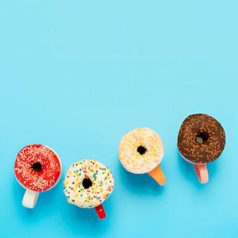 Leckere donuts und tassen mit heißen getränken auf einer blauen oberfläche. konzept von süßigkeiten, bäckerei, gebäck, kaffeestube. platz. flachgelegt, draufsicht