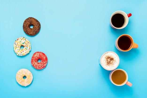 Leckere donuts und tassen mit heißen getränken isoliert