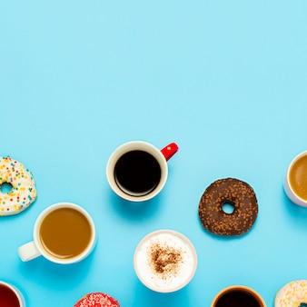Leckere donuts und tassen mit heißen getränken, kaffee, cappuccino, tee auf blau
