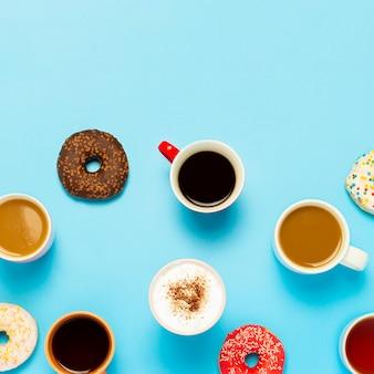 Leckere donuts und tassen mit heißen getränken, kaffee, cappuccino, tee auf blauem hintergrund. konzept von süßigkeiten, bäckerei, gebäck, café, treffen, freunde, freundliches team. quadrat. flache lage, ansicht von oben.
