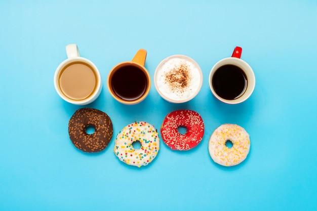 Leckere donuts und tassen mit heißen getränken, kaffee, cappuccino, tee auf einer blauen fläche. konzept von süßigkeiten, bäckerei, gebäck, café