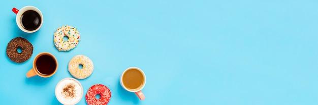 Leckere donuts und tassen mit heißen getränken, kaffee, cappuccino, tee auf einer blauen oberfläche. konzept von süßigkeiten, bäckerei, gebäck, kaffeestube, treffen, freunden, freundlichem team. flachgelegt, draufsicht