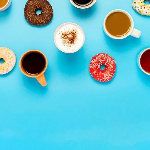 Leckere donuts und tassen mit heißen getränken, kaffee, cappuccino, tee auf einer blauen oberfläche. konzept von süßigkeiten, bäckerei, gebäck, kaffeestube, treffen, freunden, freundlichem team. platz. flachgelegt, draufsicht