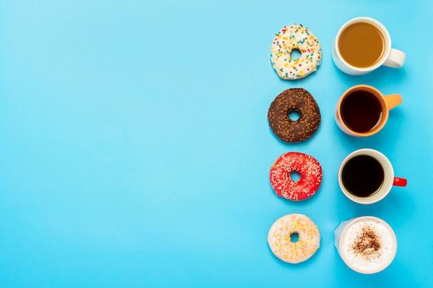 Leckere donuts und tassen mit heißen getränken, kaffee, cappuccino, tee auf einer blauen oberfläche.