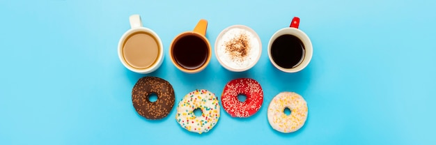 Leckere donuts und tassen mit heißen getränken, kaffee, cappuccino, tee von oben