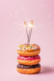 Leckere donuts zum geburtstag auf pastellrosa hintergrund.