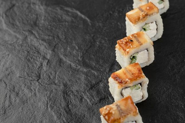 Leckere drachen-sushi-rollen mit aal auf schwarzer oberfläche