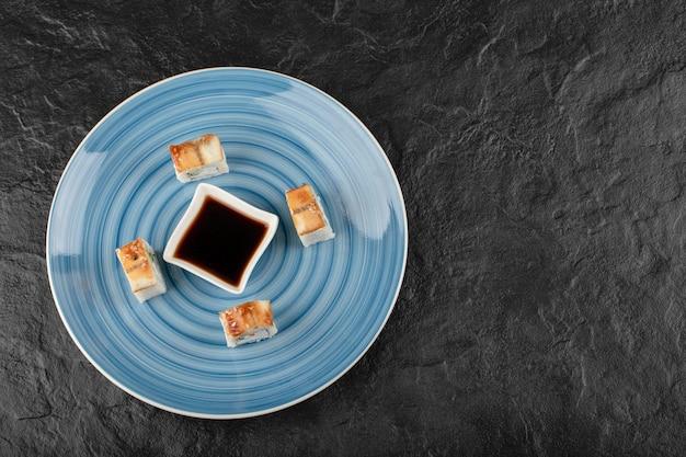 Leckere drachen-sushi-rollen und sojasauce auf blauem teller