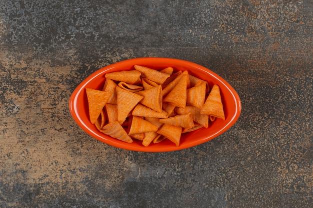 Leckere dreieckschips in orangefarbener schüssel.